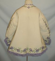 Mid 1860's ivory cashmere wool jacket. The jacket is extensively embroidered with two shades of purple flowers surround by green leaves. The neckline is trimmed with light lavender Van Dyke silk points. The wide bell shaped sleeves and hemline are decorated with lilac silk fringe. The jacket has a flared hemline. The jacket is lined in ivory silk and has a front hook and eye closure. The jacket is in very good condition. Bust 38 Waist 46 Length not including fringe 23.