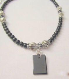 A man's gemstone necklace featuring black Obsidian beads accented with silver metal beads. In the center is an Obsidian gemstone drop pendant in size 20mmx14mm, rectangular in shape. Closes with a...@ artfire