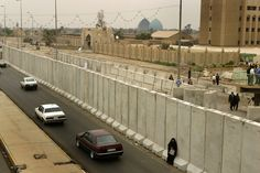"""Lucian Perkins. """"Barbed wire lines a street near the Palestine hotel. With cement walls and barbed wire going up around Baghdad to protect the Green Zone and important buildings, the city is becoming divided, reminiscent of the Berlin Wall"""". 2003. Baghdad, Iraq."""