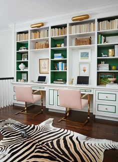 Everything about this gorgeous office and library space is perfection! Love the zebra hide rug, pink side-by-side chairs, & the emerald backdrop in the built-in shelves.