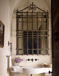 Wrought iron can be introduced in the bathroom or powder room with decorative hardware or mirrors. Here a vintage iron window grate is re-purposed cleverly ...