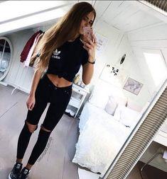 Una maglietta nera dell'Adidas ed un pantalone strappato al ginocchio.