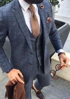 Él lleva marrón corbata con a la blazer y chaleco nosotros gris. Él trage cuesta doscientos cincuenta dólares. Él anteojos de sol cuestan lo mismo que su reloj de pulsera, treinta y uno dólares.