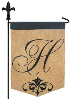 Burlap monogram garden flag featuring an elegantly designed, script letter H with an ornate scroll accent, all heavily embroidered on a textured polyester material that looks like real burlap. This fl
