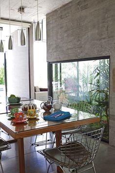 Cocina comedor integrada moderna y minimalista, con estructura de hormigón a la vista y contraste a través de un patio interno con plantas.