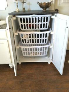 This is ingenious. Simply take an old pantry cabinet or nightstand, measure your laundry bins, and nail in 2×4′s to hold the bins up.