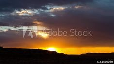 Stock Video of A static timelapse of a dramatic golden sunset and dark clouds against a contrasted and moody landscape as the sun sets below the mountain at Adobe Stock African Sunset, Sun Sets, Geology, Stock Video, Stock Footage, South Africa, Adobe, Mountain, Clouds