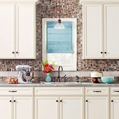 We love creamy off-white cabinets, especially when they're paired with a sophisticated stone-look laminate countertop and a glass-tile backsplash of Dark Straw Brush Strokes glass mosaics and Barrel Glass mosaic subway tiles.