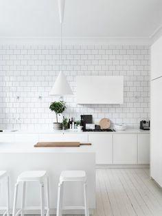 all white kitchen design // white subway tile // white pendant lights // white bar stools // white cabinets