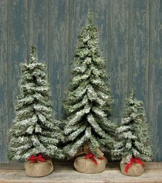 Primitive Burlap Snow Tree - 24 Inches - Short needle pine tree with dense green foliage and lightly flocked branches that mimics new fallen snow. Sturdy easy-to-pose wire branches and a wrapped burlap base with a red ribbon bow will make a perfect backdrop for your ornaments.