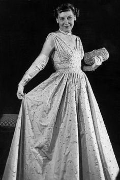 A 1953 photograph captures First Lady Mamie Eisenhower in her inaugural ball gown and carrying a jeweled purse encrusted with over 3,000 pink pearls.