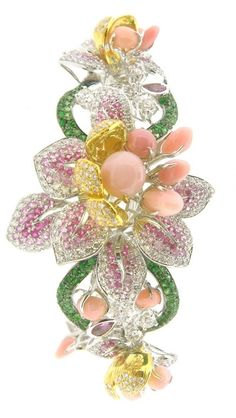 A bouquet of flowers is seen on this bracelet, decorated with natural conch shell, sapphires, tsavorites, and diamonds, Lee Jewellery
