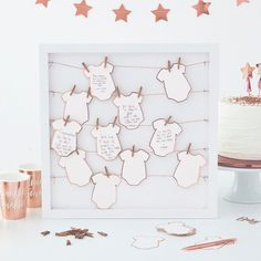 This Ginger Ray Baby Shower Guest Book Frame Kit includes a frame, tags designed to look like baby grows, pegs, and twine. Guests at your baby shower can leave their well wishes and advice with this guest book frame kit! Baby Shower Party Deko, Cadeau Baby Shower, Idee Baby Shower, Fiesta Baby Shower, Baby Party, Baby Shower Parties, Baby Boy Shower, Baby Shower Gifts, Baby Shower Frame