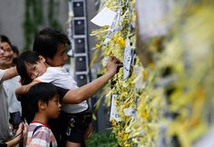 A father and his children look at yellow ribbons tied on a gate of Hong Kong's government offices