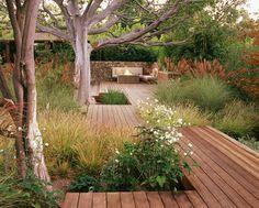 Timber boardwalk winding it's way through a perennial garden and mature trees. Pinned to Garden Design by Darin Bradbury.