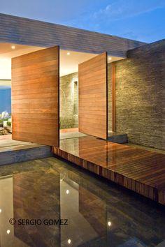 Casa moderna, en la cual se puede apreciar bien el uso de madera en las puertas y el piso deck, donde hace que se vea bastante elegante.