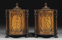 A pair of George III mahogany knife boxes,circa 1800, in the manner of George Oakley, strung with ebony, the oval panelled revolving drum containers enclosing graduated and pierced tiers within part fluted turned tapering uprights with Ionic capitals and panther mask headers, and with rising fluted reeded beaded and finialed circular canopies, on hairy paw feet.