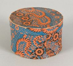 Pennsylvania wallpaper box, mid 19th c., having orange floral decoration on a blue ground, 3 3/4'' h., 6'' dia.