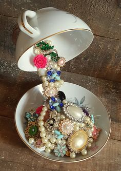 Add a delicate decoration to your home with this floating tea cup center piece. A vintage tea cup is suspended above its matching saucer, spilling out beautiful jewels and pearls. Makes a great gift!  Saucer is 6 in diameter; full height is 8.