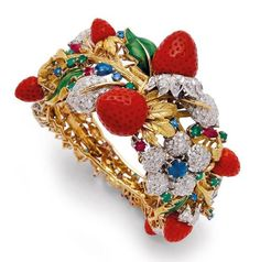 An Astounding Diamond, Sapphire, Emerald,Ruby, Coral, Enamel and Yellow Gold Bangle/Bracelet, ca.1970. The hinged hoop designed as a textured 18k gold elaborate branch embellished by coral strawberries and green enamel leaves amid flowers and foliage set with the gems mentioned purposedly placed.