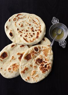 Naan indisches Fladenbrot  160 g Mehl, universal, plus Mehl zum Arbeiten ½ TL (Weinstein-)Backpulver ¼ TL Natron ½ TL Zucker (2 g) ¾ TL Salz (3,5 g) 50 ml Milch 3 EL Butter (27 g) 65 g Naturjoghurt Optional: zerlassene Butter zum Einstreichen, Knoblauchhälften