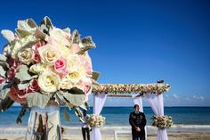 Groom wearing military uniform waiting under a gazebo for a beach wedding ceremony. Romantic pink and cream floral flower arrangements in large crystal glass vases Beach wedding at Now Sapphire  @nresortswedding with @aneltorres564 @choko7 #nowsapphire