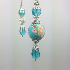Light and ceiling fan pull chains. Beautiful aqua color.    Stainless steel wire, polymer clay bead, glass faux pearl bead, aqua faceted glass beads, metal spacer beads and bead caps, and silver ball chain.  Beaded Length: 2-1/2 inches for main pull. 2 inches for coordinating pull.  Ball chain is 7 inches long.    Your item will arrive in a gift box ready for gift giving.   I can create any ceiling fan pull to match your interior. Click on the Contact button to make a request.   This…