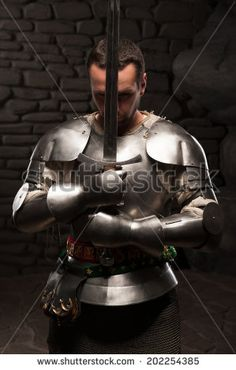 Waistup portrait of medieval knight keeping sword on chest on a dark stonewall background