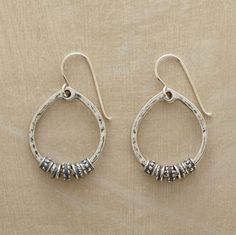 """ISIGALO EARRINGS--The carved wooden bangles of an African tribe inspired the circlets that move freely on our hand cast hoops. Sterling silver with French wires. Exclusive. 1-3/8""""L."""