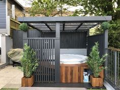 Modern grey pergola.Lazy spa hot tub, iroko surround https://www.divesanddollar.com/pool-safety-fence/