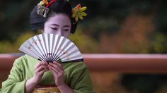 The maiko Katsuhina gracefully hide her face with a fan