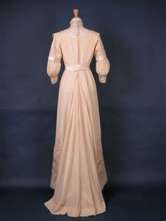 1910 ca.  Wedding Dress, Back, British.  Oyster satin with tucked bodice trimmed with heavy lace. Tucked muslin under sleeves. Shaped and draped skirt at front. Longer at back with fullness. Bodice has back fastening with hooks and eyes, four bones.  nationaltrustcollections.org.uk