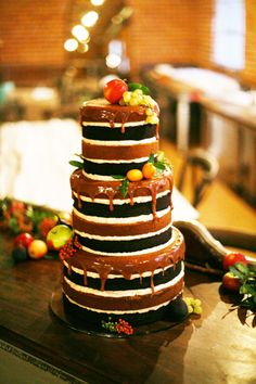 Naked Wedding Tuxedo cake. Contrasting colors set this cake apart from the rest. Topped with fresh fruits and a caramel drip effect. This cake encompasses everything great about naked cakes.  Found on superfinebakery.com