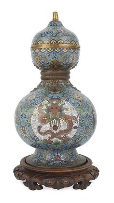 CLOISONNE DOUBLE GOURD VASE QING DYNASTY, 19TH CENTURY the sides decorated in coloured enamels with four dragon medallions, framed within scrolling stems and stylised lotus blossom reserved against a turquoise ground 40cm high