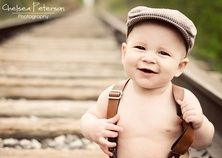 Baby newsboy hat on train track photo