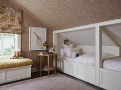 Under a sloped ceiling accented with brown grass wallpaper matching brown grass wallpaper covered walls, this beautiful shared kids' room features white built-in twin beds positioned side by side and dressed in matching white and pink hearts bedding lit by brass caged sconces.