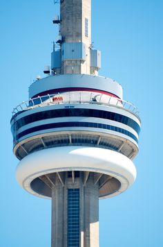 A group of people walk over the edge of the CN Tower in Toronto.