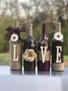 Recycled wine bottles crafted with paint, twine, and letters to spell LOVE, HOPE, HOME. This particular set is painted in espresso brown and burgundy. I will also customize with the colors of your cho Recycled Wine Bottles, Wine Bottle Art, Diy Bottle, Wine Bottle Crafts, Mason Jar Crafts, Decorative Wine Bottles, Twine Wine Bottles, Crafts With Bottles, Decorating With Wine Bottles
