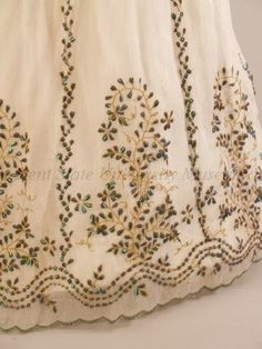 """Beetle-wing embroidered dress, 1863-67 """"Indian embroiderers have used the shimmering iridescent wings of tropical beetles, or elytra, widely in court dress since the Mughal dynasty (1526-1857). This work was much admired by British women living in India during the British colonization. In 1826, Fanny Parks was among the admirers of such work and noted that 'they embroider gowns for European ladies with these wings edged with gold; the effect is beautiful.'"""" (An Eye for Design label copy…"""