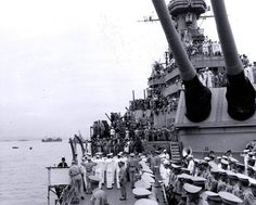 Surrender of Japan, Tokyo Bay, 2 September 1945. Surrender ceremonies in progress, as seen from USS Missouri's foredeck, with the Marine guard and Navy band in the center foreground and the ship's embarkation ladder at lower left. The backs of the Japanese delegation are visible on the 01 level deck, to the left of 16-inch gun turret # 2. Photograph from the Army Signal Corps Collection in the U.S. National Archives: SC 210628 — with Robert Gros, Michael Bone and Born Winner.