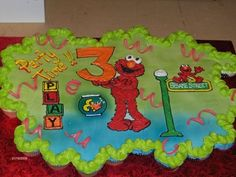 Elmo Cupcake cake...i think i like this one the best...but without the party time.. and the play blocks.. and Elmo would be carrying a 2!! and i wouldn't want the spiral things all over!! maybe some polka dots