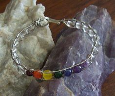 Chakra and Crystal Silver Plated Wire Wrapped Bangle  This bracelet uses Garnet, Carnelian, Yellow Calcite, Malachite,Sodalite, Amethyst and Fluorite.   Crystal Quartz is an amplifier that increases the energy of the Chakra stones.