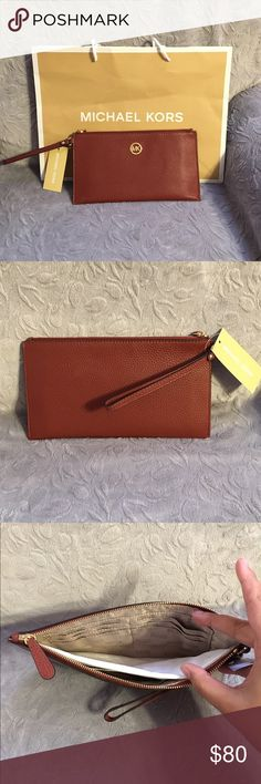 Michael Kors Jet Set Large Leather Zip Clutch Super cute leather zip clutch. Wristlet strap. One pocket on the inside. Several card holder spots. Color is a wine red. Michael Kors Bags Clutches & Wristlets