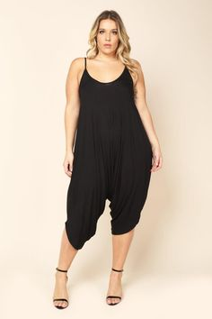 A plus size jumpsuit with a round neckline and calf-length harem pants. Solid colored and draped all throughout. Finished with hem.