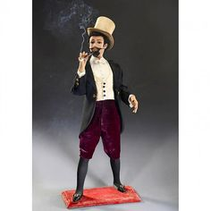 Gentleman Smoker Musical Automaton by Vichy, c. 1900  Depicting a fashionably-dressed young man with papier-mâché head, black mohair wig, beard and moustache, brown glass eyes, articulated eyelids and jaw, carrying a turned wood cheroot-holder in his right hand, the going-barrel motor in the torso playing 2 airs as the figure raises a cigarette, blinks, turns and then leans back his head to exhale, while twisting his left hand to and fro as though fanning away the smoke.