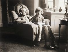 Christopher Robin sits on his father A.A Milne's lap