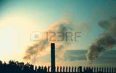 Paper mill smoke stacks illuminated by sunlight