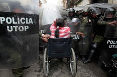 A physically disabled woman on her wheelchair clashes with riot police in the centre of La Paz.