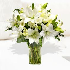This mixed white flower bouquet features lilies, gerberas, chrysanthemums, and greenery.