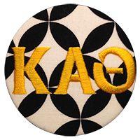 Black and white diamond eye fabric with yellow bold greek font.